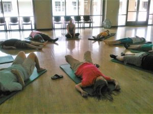 A yoga teacher sits in Sukhasana or Easy Seated Posture with a straight spine. She is surrounded by young students lying back in Savasana, a relaxing supine yogic meditation pose.