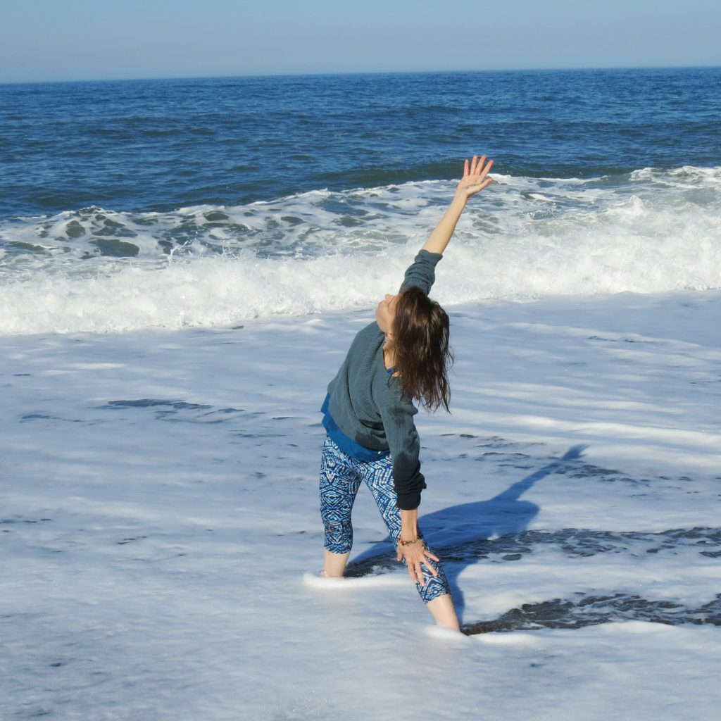 A woman practicing Triangle Pose in the ocean waves. Increased joy is one of the many benefits of private yoga.