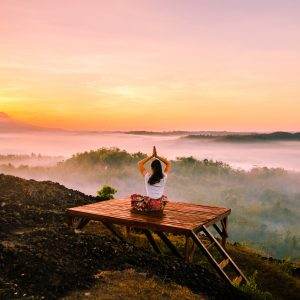 A woman sits in a serene meditation posture on a hilltop overlooking a grand foggy landscape at surise.