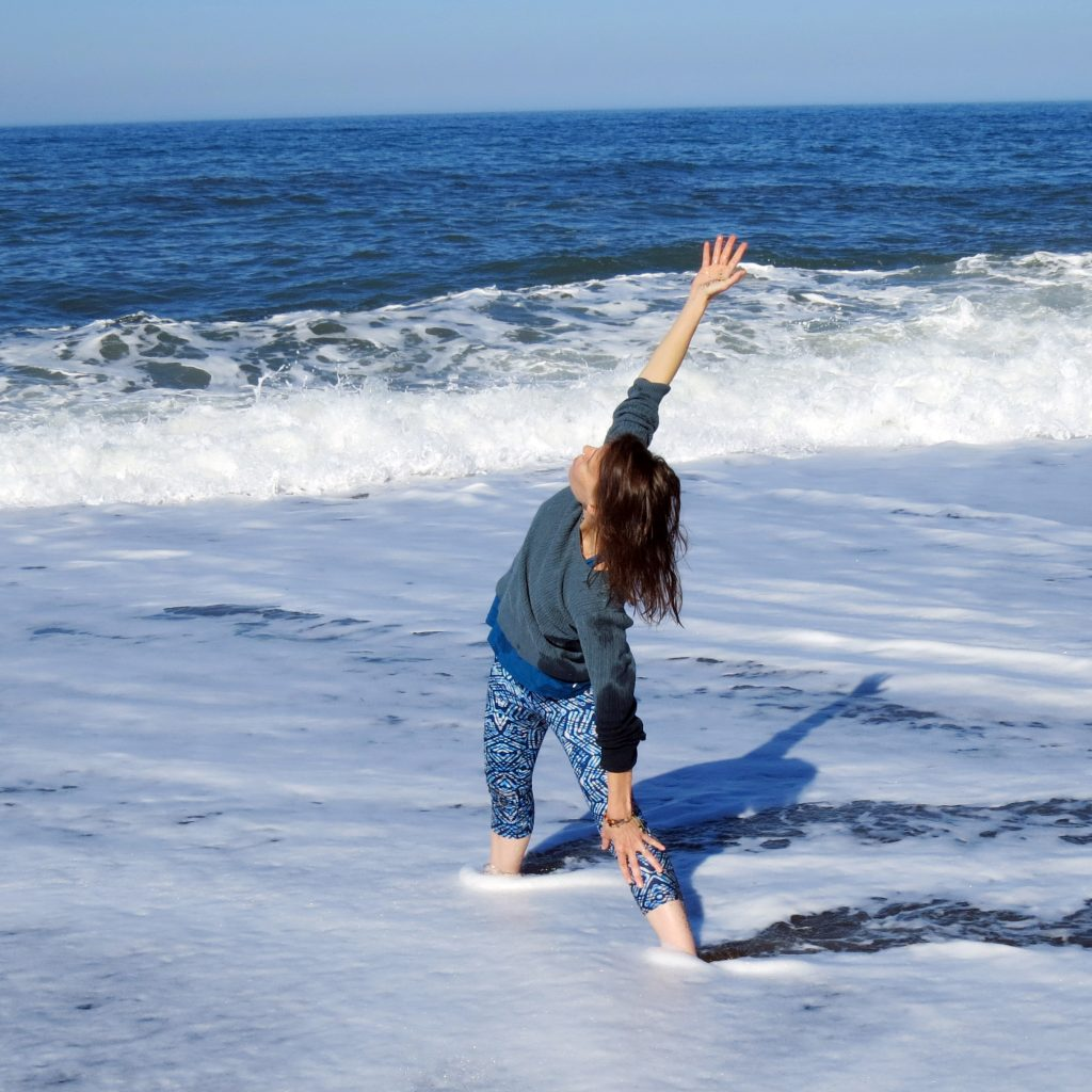 A woman practicing the yoga Triangle pose on the ocean shore.